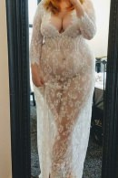 Standing in front of a mirror wearing a see through white lace dress